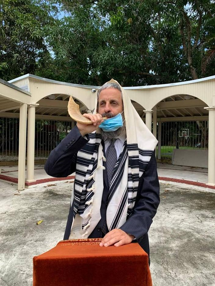 Rabbi Yossi Harlig demonstrates how he will blow the traditional shofar outside the Chabad of Kendall. The chabad will host High Holy Days services indoors and outdoors and livestream during the pandemic in September 2020.
