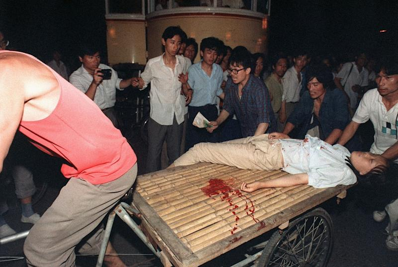 A girl wounded during the clash between Chinese PLA troops and pro-democracy students on June 4, 1989 near Tiananmen Square is carried out by a cart (AFP Photo/MANUEL CENETA)