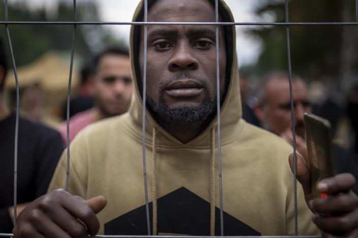 A migrant stands by the fence at the newly built refugee camp in the Rudninkai military training ground, some 38km (23,6 miles) south from Vilnius, Lithuania, Wednesday, Aug. 4, 2021. The Red Cross warned Wednesday that Lithuania's decision to turn away immigrants attempting to cross in from neighboring Belarus does not comply with international law. Lithuania, a member of the European Union, has faced a surge of mostly Iraqi migrants in the past few months. Some 4,090 migrants, most of them from Iraq, have crossed this year from Belarus into Lithuania. (AP Photo/Mindaugas Kulbis)