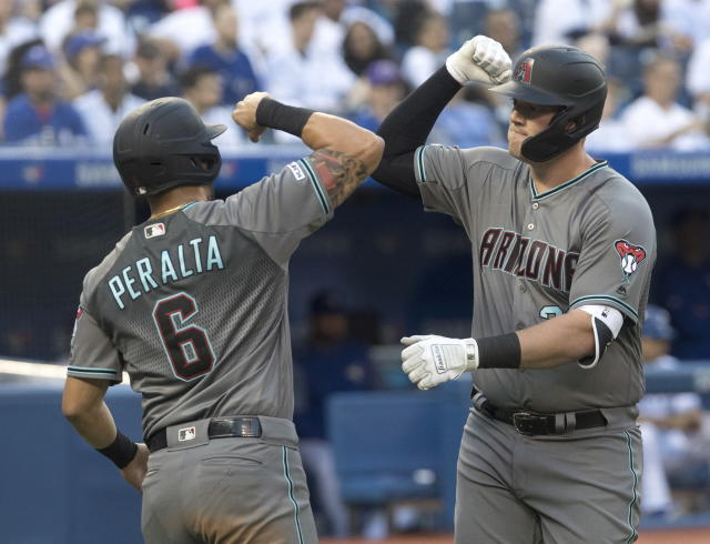 Arizona Diamondbacks' Kevin Cron, right, is greeted at home plate by David Peralta (6) after hitting a three run home run against the Toronto Blue Jays in the fourth inning of a baseball game Friday, June 7, 2019, in Toronto. (Fred Thornhill/The Canadian Press via AP)