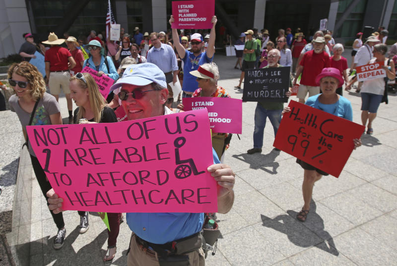 FILE - In this June 27, 2017 file photo people march during a protest against the Republican bill in the U.S. Senate to replace President Barack Obama's health care law in Salt Lake City. The Trump administration will allow Medicaid expansion with a work requirement in Utah, a decision that came Monday, Dec. 23, 2019, despite courts taking a dim view of the requirement in other states. (AP Photo/Rick Bowmer,File)