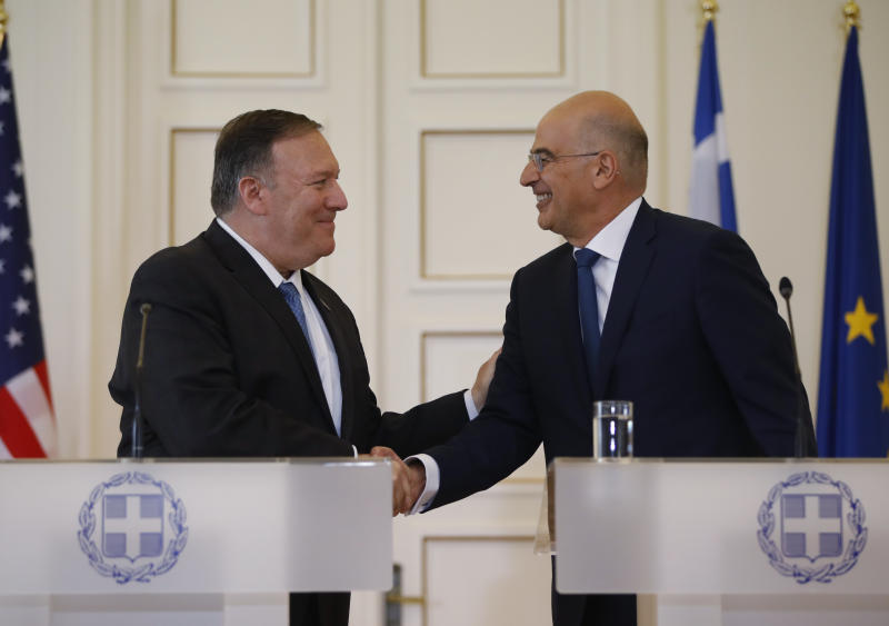 Greek Foreign Minister Nikos Dendias, right, shakes hands withU.S. Secretary of State Mike Pompeo, right, following their joint news conference after their meeting at the Foreign Ministry in Athens, Saturday, Oct. 5, 2019. Pompeo is in Greece on the last leg of a four-nation European tour that has been overshadowed by the impeachment inquiry in Washington. (AP Photo/Thanassis Stavrakis)