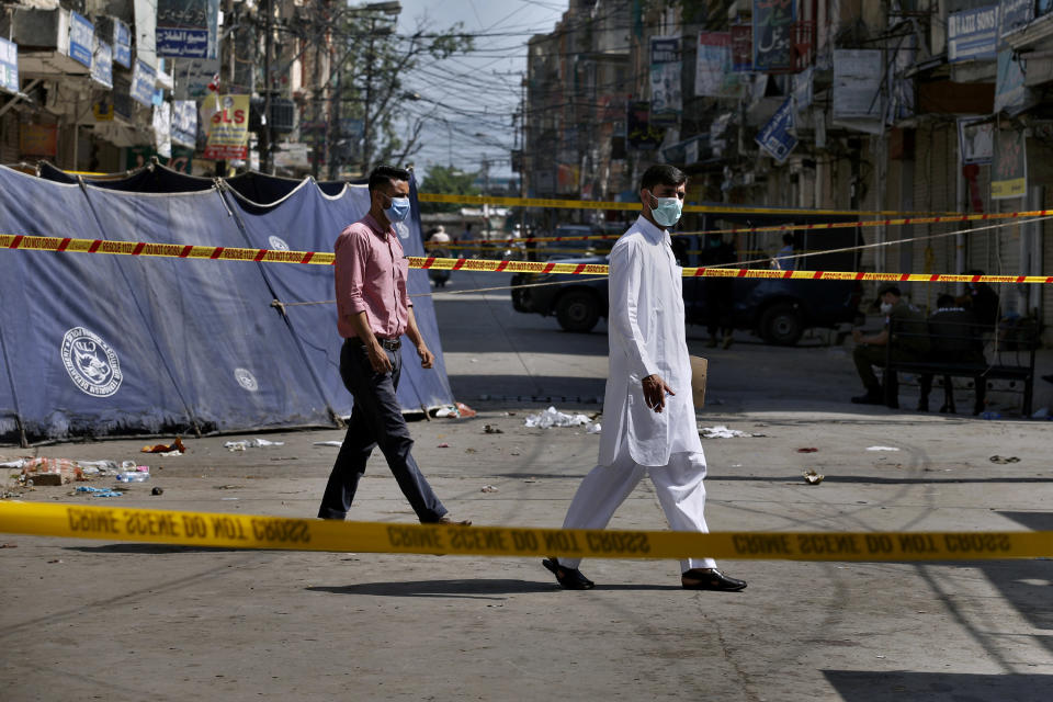 Pakistani investigators examine at the site of Friday's bomb explosion in Rawalpindi, Pakistan, Saturday, June 13, 2020. A powerful bomb exploded at a crowded bazaar in the Pakistani garrison city of Rawalpindi on Friday, killed and wounded some persons, police and government officials said. (AP Photo/Anjum Naveed)