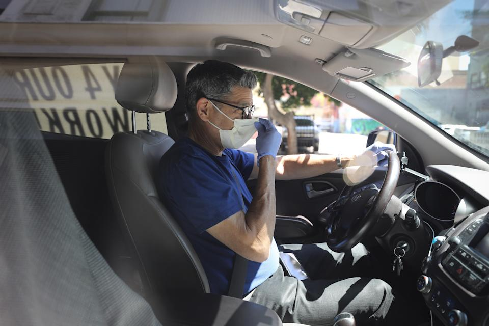LOS ANGELES, CALIFORNIA - APRIL 16: A driver adjusts his face mask as Uber and Lyft drivers with Rideshare Drivers United and the Transport Workers Union of America conduct a 'caravan protest' outside the California Labor Commissioner's office amidst the coronavirus pandemic on April 16, 2020 in Los Angeles, California. The drivers called for California to enforce the AB 5 law so that they may qualify for unemployment insurance as the spread of COVID-19 continues. Drivers also called for receiving back wages they say they are owed. (Photo by Mario Tama/Getty Images)