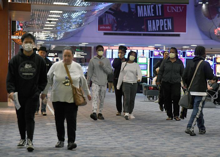 Travelers walk through a concourse at McCarran International Airport as the coronavirus spreads across the USA on March 19 in Las Vegas.