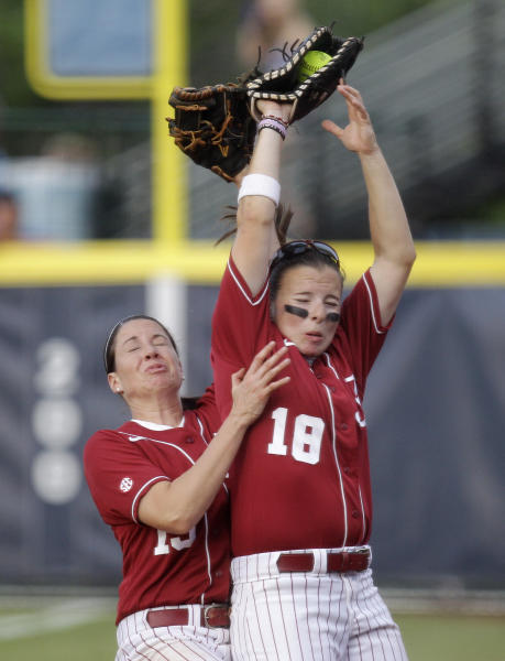 Alabama's Danae Hays (15) and Cassie Reilly-Boccia (18) collide after Reilly-Boccia caught a ball hit by Oklahoma's Georgia Casey for an out in the third inning of the second game of the NCAA Women's College World Series softball finals in Oklahoma City, Tuesday, June 5, 2012. (AP Photo/Sue Ogrocki)