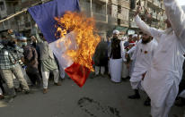 Supporters of religious group burn a representation of a French flag during a rally against French President Emmanuel Macron and republishing of caricatures of the Prophet Muhammad they deem blasphemous, in Karachi, Pakistan, Friday, Oct. 30, 2020. Muslims have been calling for both protests and a boycott of French goods in response to France's stance on caricatures of Islam's most revered prophet. (AP Photo/Fareed Khan)