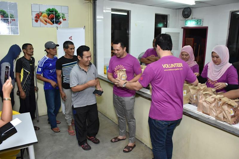 Volunteers from Universiti Kebangsaan Malaysia distribute packs of food to the homeless. — Picture by Azneal Ishak