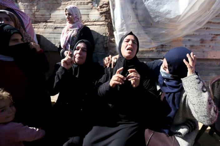 Relatives of three Palestinian fishermen from Allaham family mourn during their funeral in Khan Younis in the southern Gaza Strip