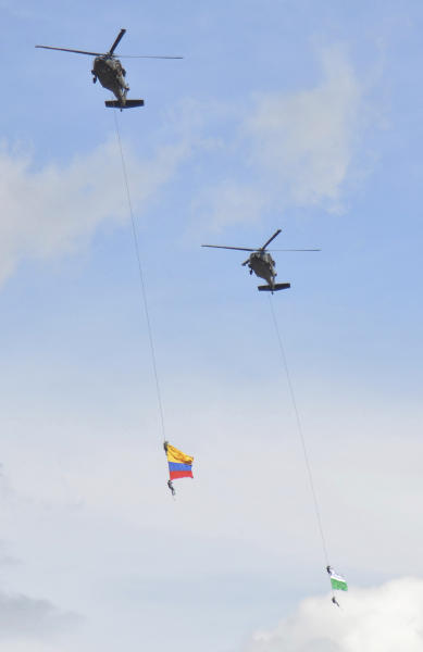 Two members of Colombia´s air force hang from a cable under a helicopter flying a Colombian flag, left, before plunging to their deaths when the cable snapped during the mid-air stunt at the Medellin Flower Fair in Medellin, Colombia, Sunday, Aug. 11, 2019. (AP Photo/Luis Benavides)