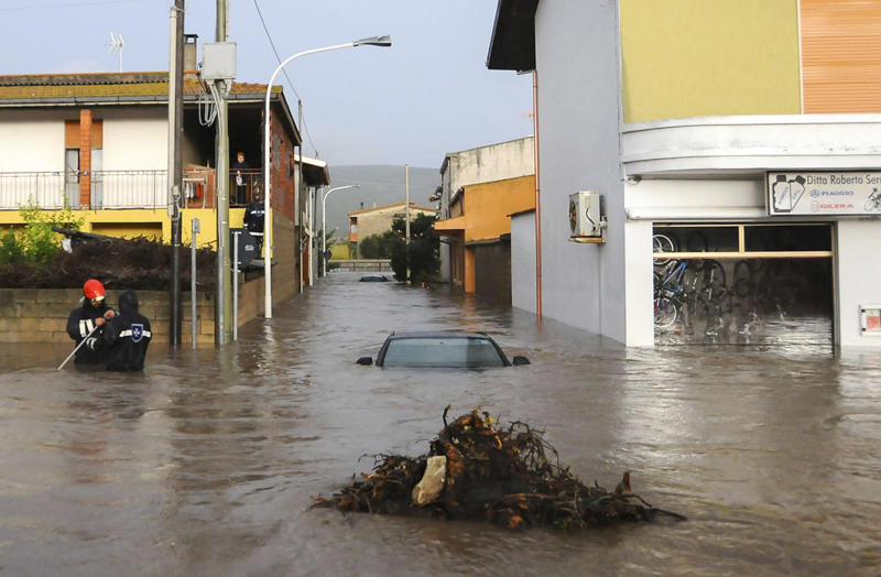 Rescuers work in a flooded street in the small town of Uras, Sardinia, Monday, Nov. 18, 2013. A violent rainstorm that flooded entire parts of the Mediterranean island of Sardinia has led to the deaths of at least nine people. Bridges were felled by swollen rivers and water levels reached 3 metres (yards) in some places. (AP Photo/Alessandra Chergia)