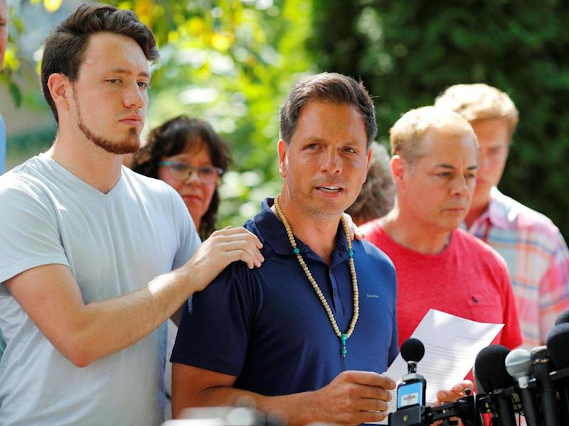 Don Damond is comforted by his son Zach Damond as he speaks to the media about his fiance Justine Damond (REUTERS/Adam Bettcher)