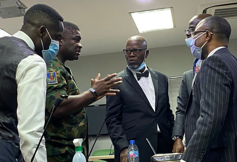 Brigadier General Ahmed Taiwo speaks with the counsel for the Nigerian Army, Akinlolu Kehinde and others during a judicial panel in Lagos