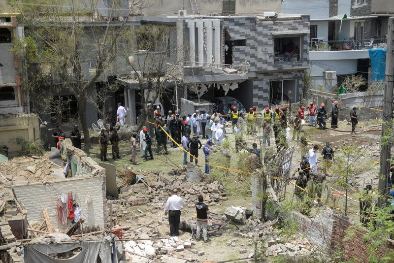 Security officials and rescue workers survey the site after a blast in a residential area in Lahore