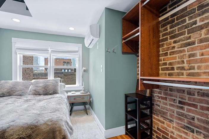 A bedroom with blue walls, exposed brick on the left and two windows in the back