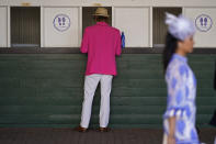 A man places a bet before the 147th running of the Kentucky Derby at Churchill Downs, Saturday, May 1, 2021, in Louisville, Ky. (AP Photo/Charlie Riedel)