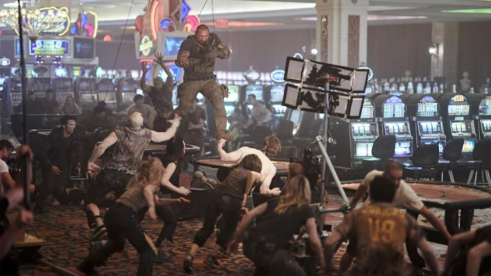 Dave Bautista hangs from wires above a group of zombies during a stunt in a behind-the-scenes still from Army of the Dead.