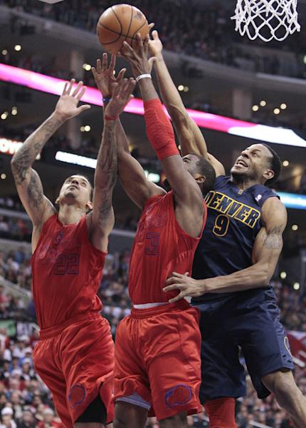 Los Angeles Clippers players Matt Barnes (22) and Chris Paul (3) fight for a rebound with Denver Nuggets' Andre Iguodala (9) during the first half of their NBA basketball game, Tuesday, Dec. 25, 2012, in Los Angeles. (AP Photo/Jason Redmond)