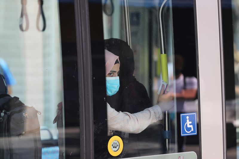 FILE PHOTO: A passenger wearing a protective mask is seen through a window as she travels on the light rail in Jerusalem amid the spread of the coronavirus disease (COVID-19)