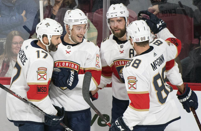Florida Panthers defenseman Aaron Ekblad (5), celebrates with center Derek MacKenzie (17), center Colton Sceviour (7) and left wing Jamie McGinn (88) after scoring against the Montreal Canadiens during first-period NHL hockey game action in Montreal, Monday, March 19, 2018. (Graham Hughes/The Canadian Press via AP)