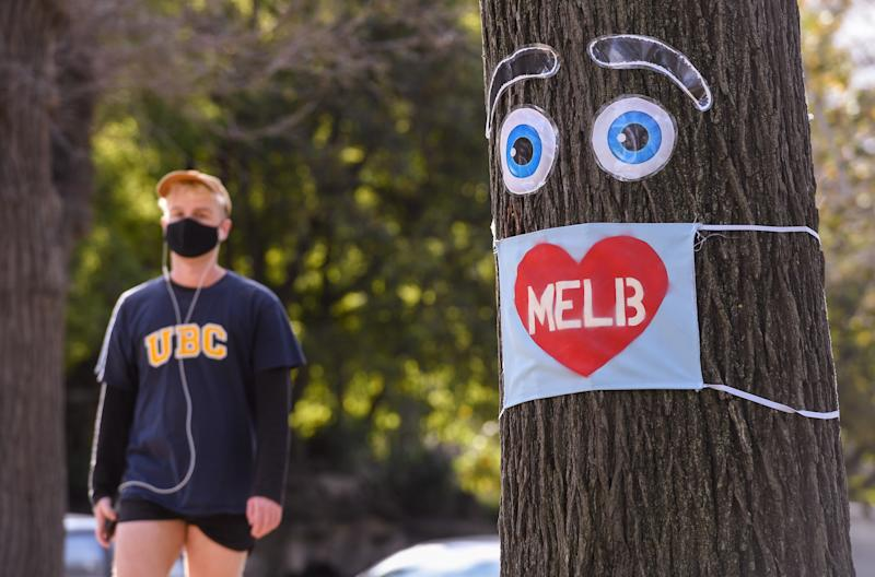 A man walks past a large face mask pinned to a tree in Melbourne on August 3, 2020 after the state announced new restrictions as the city battles fresh outbreaks of the COVID-19 coronavirus