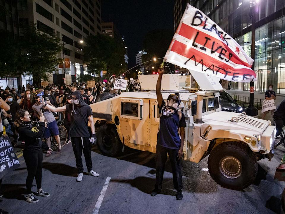 A protester waves a DC flag with Black Lives Matter spray painted on it next to a DC National Guard Humvee as protestors march through the streets during a demonstration over the death of George Floyd on 2 June 2020 in Washington, DC: Samuel Corum/Getty