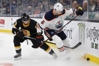 Boston Bruins' Brad Marchand (63) battles Edmonton Oilers' Adam Larsson (6) for the puck during the first period on an NHL hockey game in Boston, Saturday, Jan. 4, 2020. (AP Photo/Michael Dwyer)