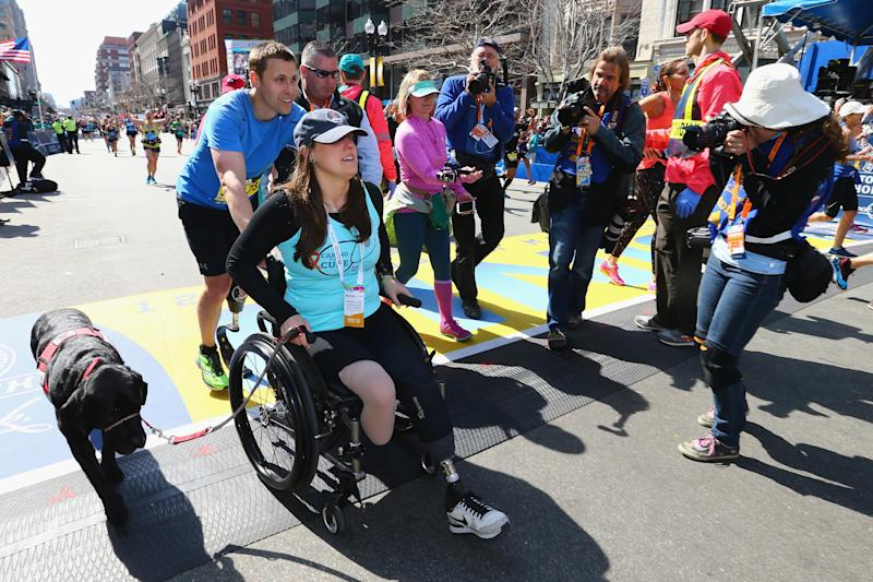 Downes and Kensky celebrate at the finish line with their dog after Downes completed the 120th Boston Marathonin 2016. (Maddie Meyer / Getty Images)