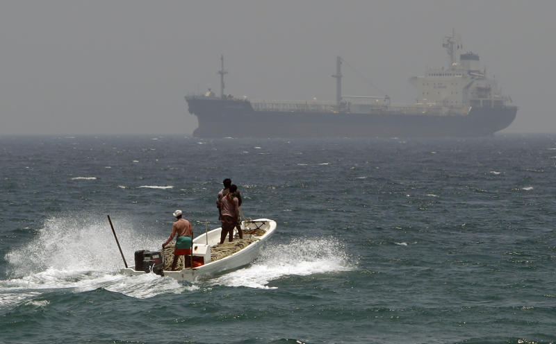 With an oil tanker in background, fishermen cross the sea waters off  Fujairah, United Arab Emirates, Wednesday, May 30, 2012. The United Arab Emirates is nearing completion of a pipeline through the mountainous sheikdom of Fujairah that will allow it to reroute the bulk of its oil exports around the Strait of Hormuz at the mouth of the Gulf, the path for a fifth of the world's oil supply. (AP Photo/Kamran Jebreili)