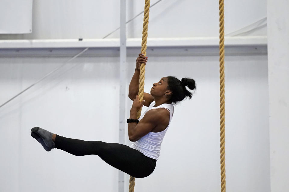 Reigning Olympic champion gymnast Simone Biles climbs a rope during a training session Tuesday, May 11, 2021, in Spring, Texas. (AP Photo/David J. Phillip)