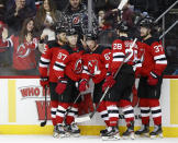 New Jersey Devils teammate celebrate with left wing Jesper Bratt (63), center, after Bratt scored a game-tying goal during the second period of an NHL hockey game against the San Jose Sharks, Thursday, Feb. 20, 2020, in Newark, N.J. (AP Photo/Kathy Willens)