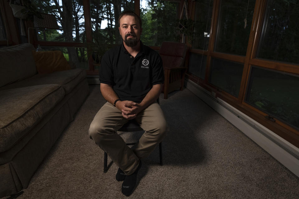 Korey Rowe poses for a photo at his home in Oneonta, N.Y. on Thursday, Aug. 12, 2021. Korey Rowe served tours in Iraq and Afghanistan and returned to the U.S. in 2004 traumatized and disillusioned. His experiences overseas and nagging questions about Sept. 11, 2001 convinced him America's leaders were lying about what happened that day and the wars that followed. (AP Photo/Robert Bumsted)