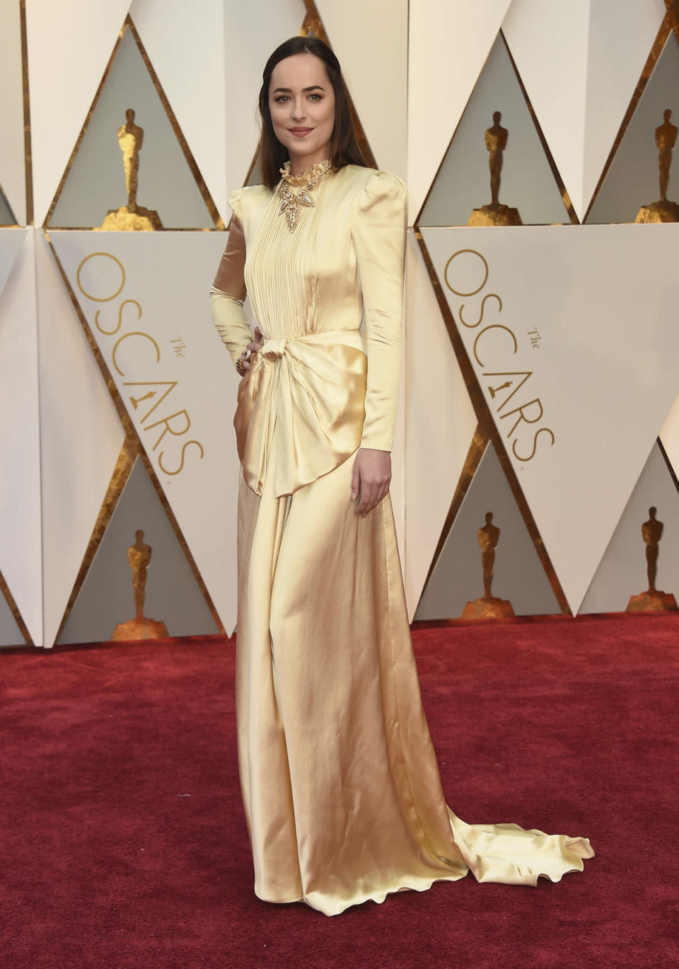 <p>Dakota Johnson, star of <em>Fifty Shades Darker</em>, completely covered up in a long-sleeved gold gown from Gucci. <em>(Photo: Getty Images)</em> </p>