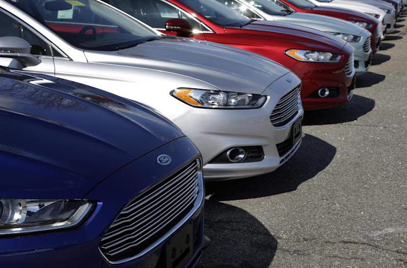 In this Wednesday, March 20, 2013 photo a row of Ford Fusion sedans sit in a lot at a Ford dealership in, Norwood, Mass.  General Motors Co. and Ford Motor Co. have agreed Monday, April 15, 2013,  to jointly design nine- and 10-speed automatic transmissions for cars and trucks. The companies will build the transmissions separately. (AP Photo/Steven Senne)
