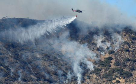 Flames threaten California coastal communities as firefighters mourn