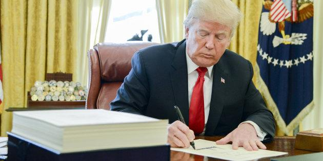 U.S. President Donald Trump signs a tax-overhaul bill into law in the Oval Office of the White House in Washington, D.C., Fri. Dec. 22, 2017.
