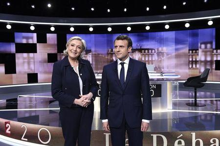 Candidates for the 2017 presidential election, Emmanuel Macron (R), head of the political movement En Marche !, or Onwards !, and Marine Le Pen, of the French National Front (FN) party, pose prior to the start of a live prime-time debate in the studios of French television station France 2, and French private station TF1 in La Plaine-Saint-Denis, near Paris, France, May 3, 2017.    REUTERS/Eric Feferberg/Pool