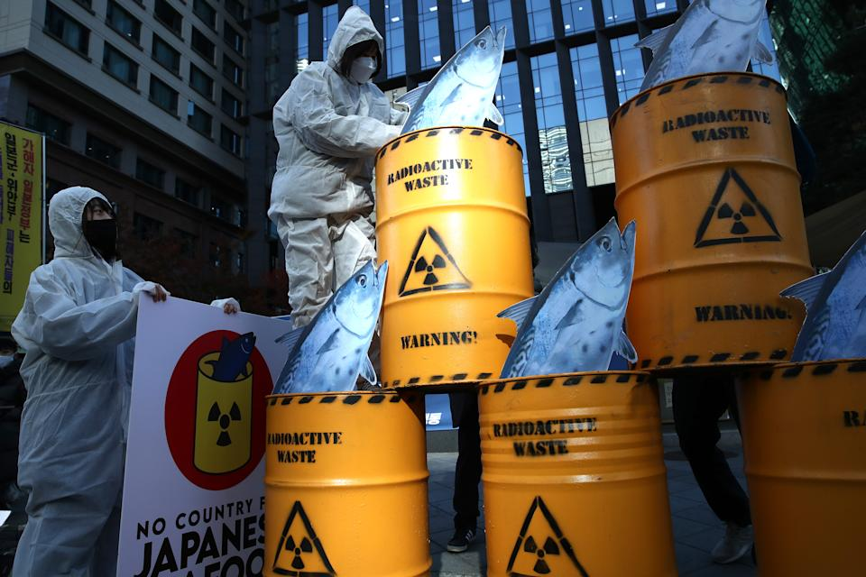 SEOUL, SOUTH KOREA - NOVEMBER 09: South Korean environmentalists with mock nuclear waste drum containers stage a rally against Japan's disposal of radioactive water plan at the Fukushima nuclear power, in front of Japanese embassy on November 09, 2020 in Seoul, South Korea. Activists to call on the Japanese government to retract its plan to release water containing radioactive materials stored at the Fukushima nuclear power plant in Japan. (Photo by Chung Sung-Jun/Getty Images)