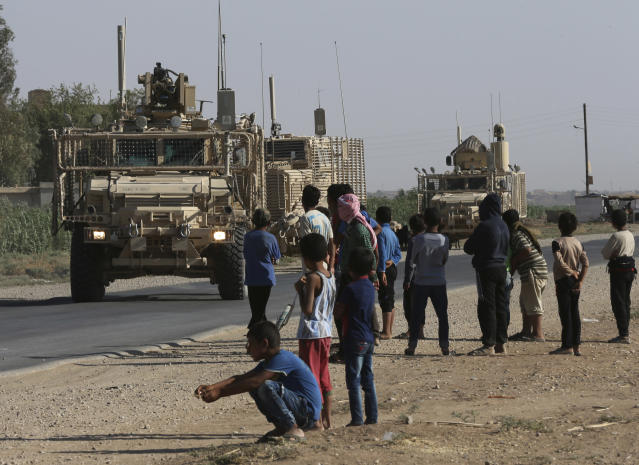 FILE - In this July 26, 2017, file photo, Syrian children and youths watch a U.S. armored vehicle convoy passing on a road that links to Raqqa, northeast Syria. (AP Photo/Hussein Malla, File)