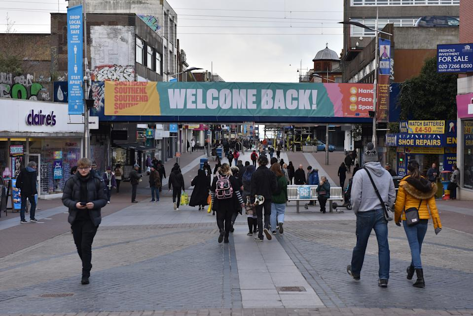 SOUTHEND, ENGLAND - APRIL 12: People walk on the high street under a bridge with a banner saying