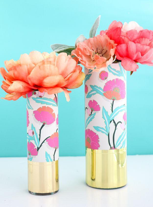 "<p>Blogger Kara Whitten of <a href=""https://akailochiclife.com/2016/07/diy-it-wrapped-patterned-vases.html"" rel=""nofollow noopener"" target=""_blank"" data-ylk=""slk:Kailochic"" class=""link rapid-noclick-resp"">Kailochic</a> used small wallpaper samples from Spoonflower to decorate a glass cylindrical vase. She wrapped the top part in a peel-and-stick floral print and the bottom in gold foil. These vases would make the perfect gift! <br></p>"
