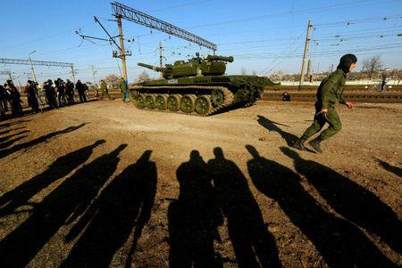 A Russian tank crew member runs in front of his T-72B tank after their arrival in Crimea in the settlement of Gvardeiskoye near the Crimean city of Simferopol
