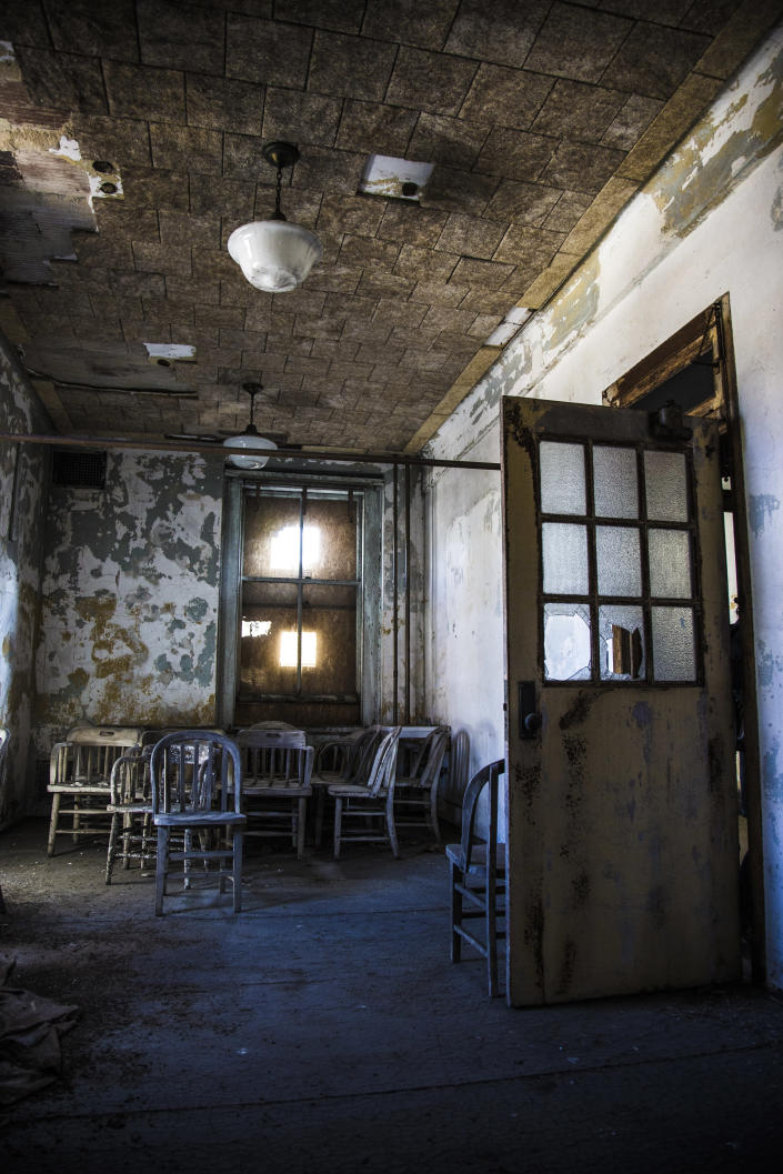 <p>A room at the end of a hallway is filled with old chairs. (Photo: Gordon Donovan/Yahoo News) </p>