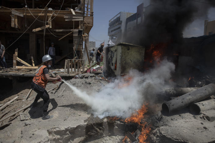 A Palestinian firefighter extinguishes a fire from a beachside cafe after it was hit by an Israeli airstrike, in Gaza City, Monday, May 17, 2021. (AP Photo/Khalil Hamra)