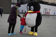 A child leans on a mascot for Tencent during a promotion event in Beijing on Wednesday, Nov. 11, 2020. China is banning children from playing online games for more than three hours a week, the harshest restriction so far on the game industry as Chinese regulators continue cracking down on the technology sector. (AP Photo/Ng Han Guan)