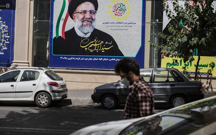 A man walks by a campaign office of Ebrahim Raisi who today was named as the winner of the Iranian Presidential Election, in Tehran - Sam Tarling/Sam Tarling for The Telegraph