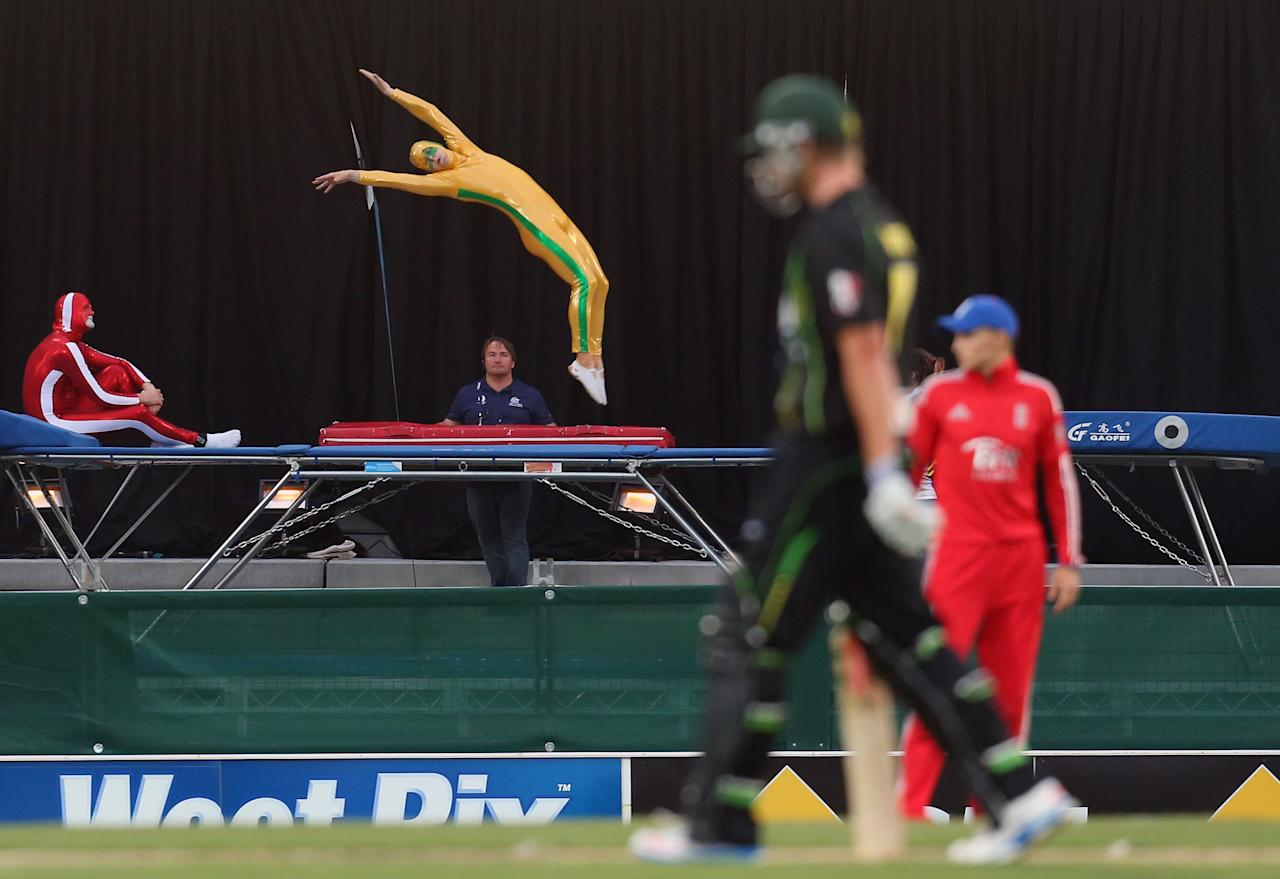 HOBART, AUSTRALIA - JANUARY 29:  Acrobats on a trampoline perform after Cameron White of Australia hit a boundary during game one of the International Twenty20 series between Australia and England at Blundstone Arena on January 29, 2014 in Hobart, Australia.  (Photo by Scott Barbour/Getty Images)