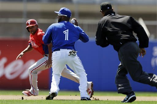 Toronto Blue Jays second baseman Emilio Bonifacio (1) throws to second to make the out on Philadelphia Phillies' Ben Revere, rear, after Chase Utley hit into a first-inning fielder's choice in a spring training exhibition baseball game in Dunedin, Fla., Monday, March 25, 2013. (AP Photo/Kathy Willens)