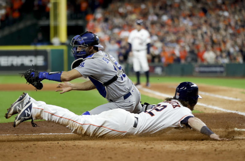 Houston's Josh Reddick slides safely past Dodgers catcher Austin Barnes to score on Marwin Gonzalez's second-inning single. (AP)