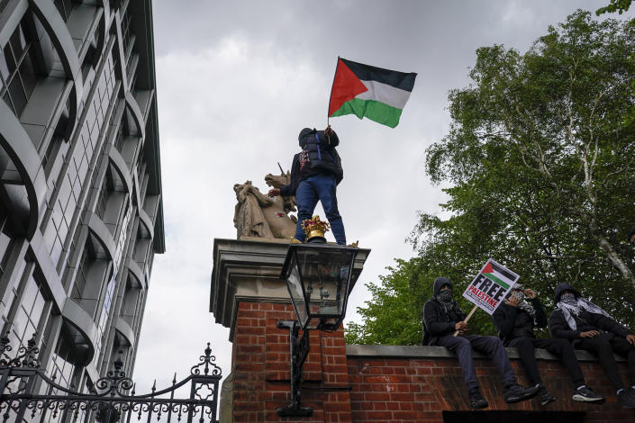 People hold placards and Palestinian flags during a march in solidarity with the Palestinian people amid the ongoing conflict with Israel, during a demonstration in London, Saturday, May 15, 2021. (AP Photo/Alberto Pezzali)